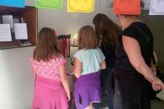 Escape game Alexandra David-Néel : Une mère et ses trois filles cogitent sur la valeur du travail et l'importance de l'éducation pour les femmes, prônées par Alexandra David-Néel dans ses articles féministes.
