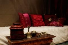 près du lit : table tibétaine en bois sculpté et objets rituels + tsampa