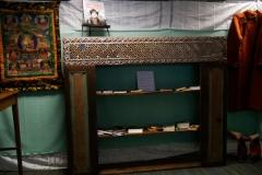 Bibliothèque avec les ouvrages consultables d'Alexandra David-Néel, bottes tibétaines et Goncha
